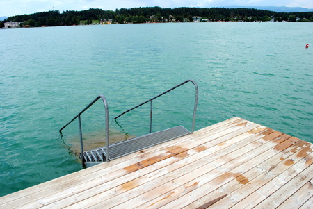 steel ladder with blue lake on background Stock Photo