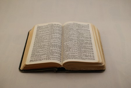 Opened holy bible laying on a white background