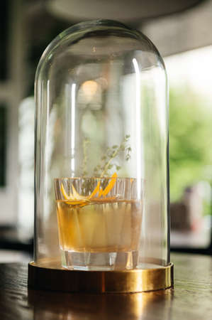 Whiskey & Smoke. Autumn old fashion with orange and thyme. Experimental alcoholic cocktail in a flask with smoke on the table in restaurant