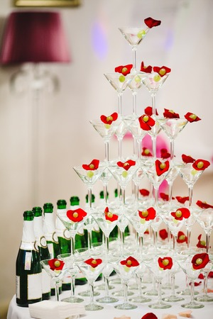 wedding reception decoration: Pyramid glasses of champagne with olives and rose petals