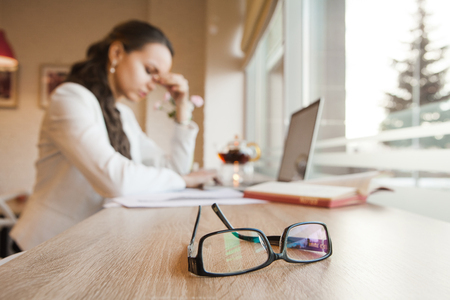 superintendent: Black-rimmed glasses lie on table against background of girl with headache Stock Photo