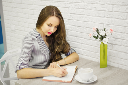 arm bouquet: Sympathetic girl holding pen and writting in sketch-book