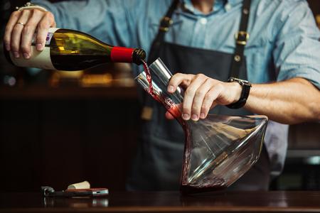 Sommelier, der Rotwein in Karaffe gießt, um eine perfekte Farbe zu erhalten