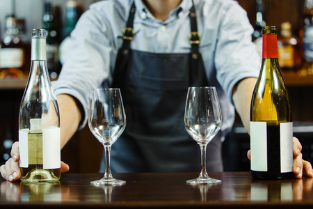 sommeliers: male sommeliers holds white and red wine