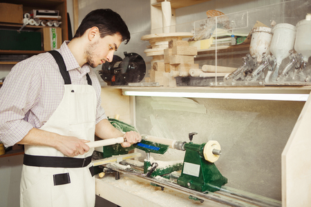 Young turner engages in wood carving on lathe for wood