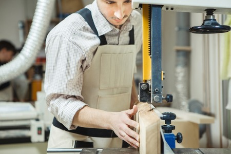 cut off saw: Dark-haired man holding timber on band saw