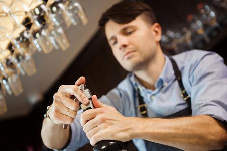 bottle opener: Male sommelier open wine bottle with corkscrew.