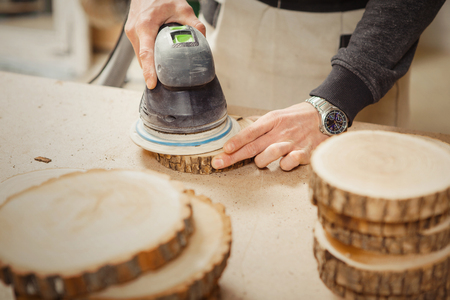 Male holding wooden round workpiece and processing with grinding machine Stock Photo