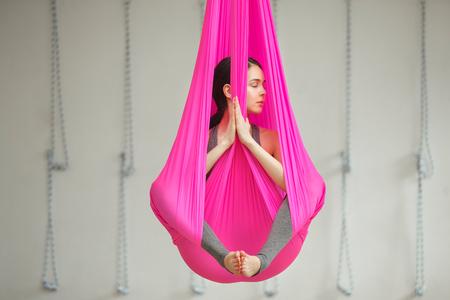 Girl lotus pose aerial antigravity yoga. Woman sits in hammock