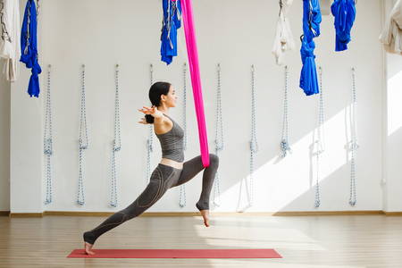 Adult woman practices inversion anti-gravity yoga position
