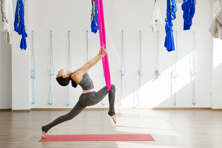 Girl stretching legs with help of hammock. Aerial exercise yoga