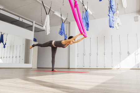 safety harness: Adult woman practices balancing stick anti-gravity yoga position in studio