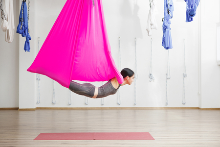 Adult woman practices anti-gravity yoga position in gym. Standard-Bild