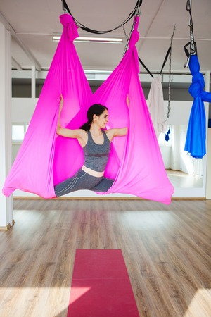 Young woman making antigravity yoga exercises with pink hammock