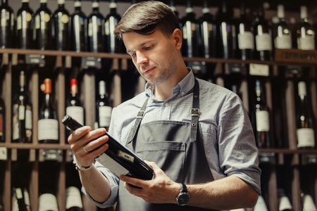 Young sommelier holding bottle of red wine in cellar