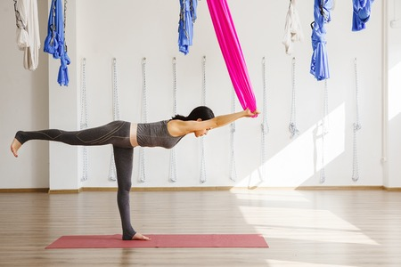 Adult woman practices balancing stick anti-gravity yoga position in studio