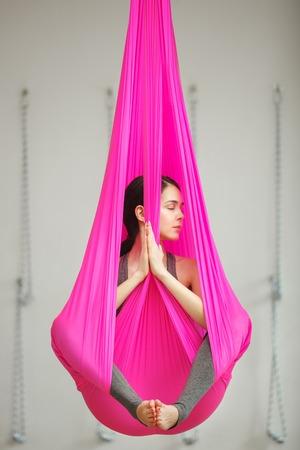 gravedad: El loto de la muchacha plantea el yoga antigravity aéreo. La mujer se sienta en la hamaca Foto de archivo