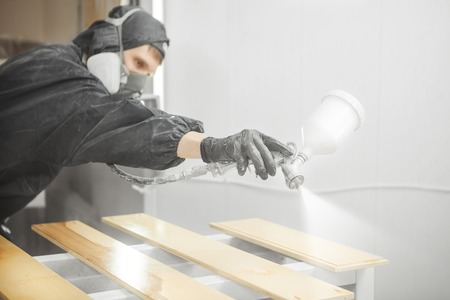 Man in respirator mask painting wooden planks at workshop. Stockfoto