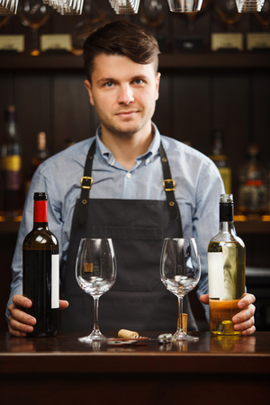 degustation: Sommelier with bottles of red and white wine and wineglasses