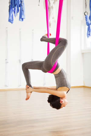 Inversion pigeon pose in aero anti gravity yoga. Woman hangs upside down. Aerial yoga exercise made with help of pink hammock. Young girl in grey sport suit does trainings 版權商用圖片