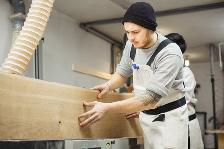 Worker processes board on woodworking machine