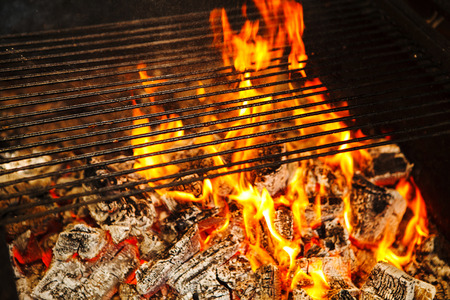 Burning logs in fire covered by grid on top, horisontal cast iron grill and burning flame from hot woods, comfortable warm place, decoration in house interior Stock Photo