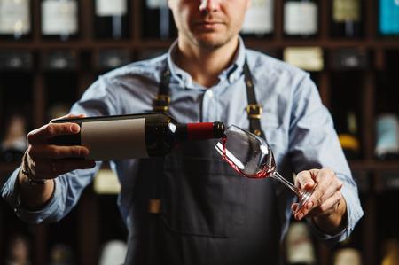 Sommelier macho vertiendo vino tinto en copas de tallo largo. Camarero con una botella de bebida alcohólica. Camarero en la barra del bar vierte bebida de élite en vaso de tallo largo
