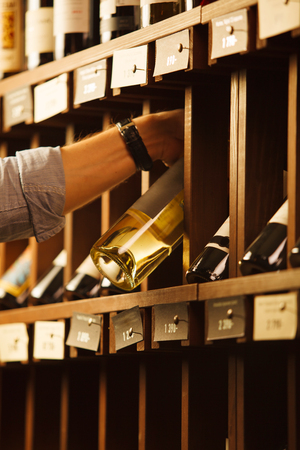 elite: Expert in winemaking choose elite white wine in cellar. Males hand on background of shelves with wine, sommelier at work Stock Photo