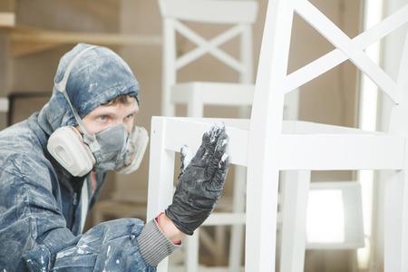 남자는 호흡 마스크에서 페인트 도포의 균일 성을 검사합니다. 난연제의 적용으로 화재 방지, 에어리스 스프레이 장치를 보장합니다. 스톡 콘텐츠