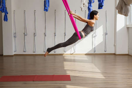 Adult woman practices inversion yoga position in gym. Aerial antigravity yoga girl on pink silk hammock, doing exercises, meditating in calm position of relaxed flying body