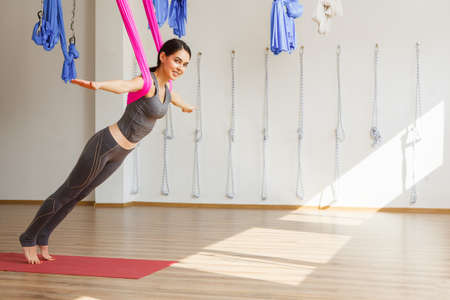 Adult woman practices aero yoga position in studio. Girl stretches back with help of hammock in gym, aerial yoga concept