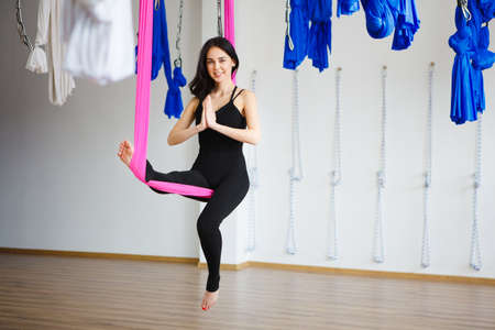 Young female person in pink hammock sits in position with attached hands and does aero yoga. Sport exercise, keeping balance on hanging material