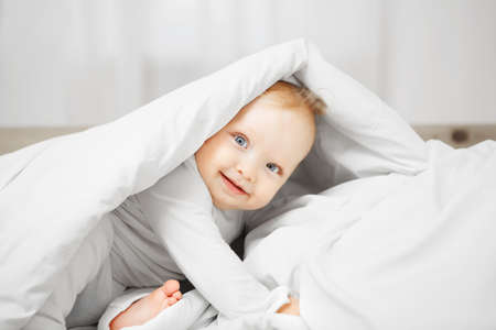 Playful baby with big light eyes, excited look and plump cheeks sits on comfortable bed and hides under warm blanket dressed in white crawlers.
