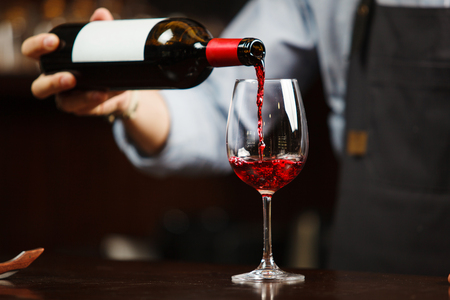 Waiter pouring red wine into wineglass. Sommelier or bartender pours alcoholic drink without splashes into glassware utensil Stock Photo