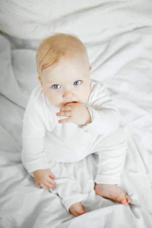 Charming baby with big light kind eyes, plump cheeks and fair blond hair dressed in white crawlers sits on comfortable bed portrait from above.