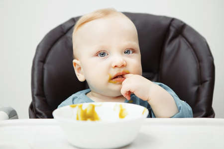Adorable baby with big light eyes sits in high chair and eats vegetable cream soup from deep bowl. Little kid takes big spoon in mouth photo. 版權商用圖片