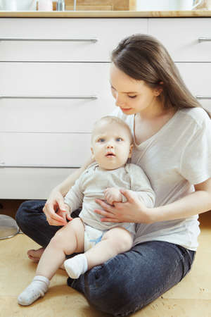Woman sitting on floor with little baby on her arms, happy motherhood concept. Mother and her adorable child spend time together 版權商用圖片