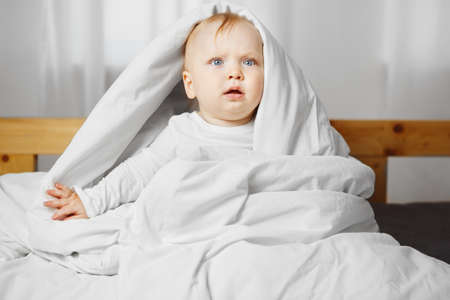 Cute baby with bewildered air, blond hair and big light grey eyes sits on spacious soft bed and looks out warm blanket dressed in white crawlers.