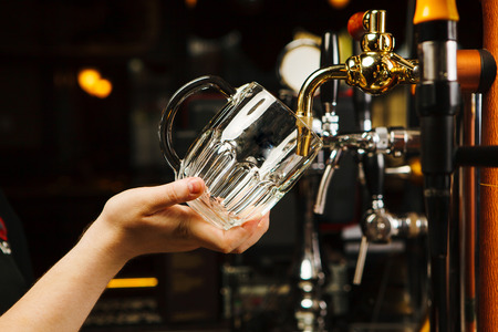 Barman going to pour beer into glass goblet from tap, closeup hands of male with transparent mug near bar counter with golden faucet Stock Photo