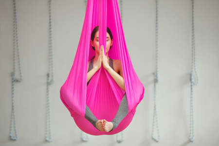 Girl in lotus pose aerial antigravity yoga. Woman sits in pink silk hammock, does exercises, meditate in calm position trying to achieve peaceful state of mind and body Banco de Imagens