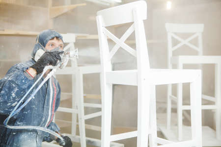 Man painting chair into white paint in respiratory mask. Application of flame retardant ensuring fire protection, airless spraying device. Banco de Imagens
