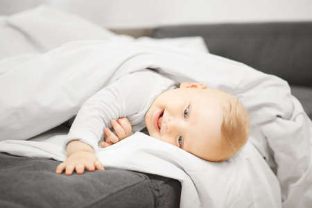 Playful baby with funny face expression lies on soft couch under warm blanket and looks at his hand. Hilarious little kid in cheerful mood photo.
