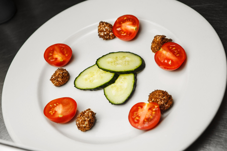 Preparation of salad with cucumbers, and cherry tomatoes, roasted pieces of bread on white plate, healthy organic dieting meal closeup view