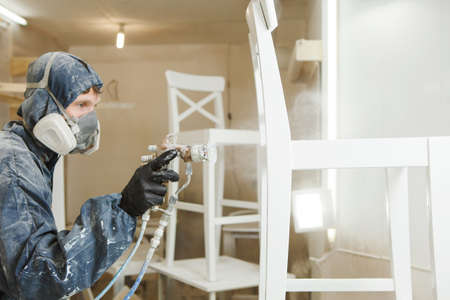 Man painting chair into white paint in respiratory mask. Application of flame retardant ensuring fire protection, airless spraying device. Banque d'images