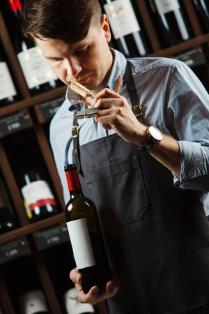 Sommelier smelling flavor of cork from red wine