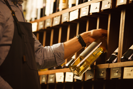 Expert in winemaking choose elite white wine in cellar. Males hand on background of shelves with wine, sommelier at work Stock Photo