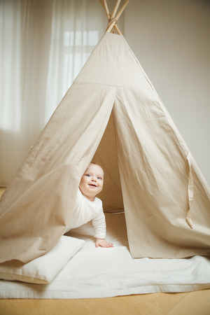 Curious child peeps into the childrens tent full of pillows Stock Photo