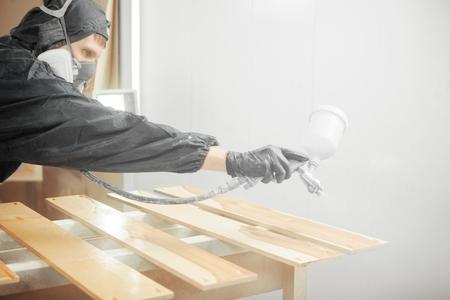 Man in respirator mask painting wooden planks at workshop. Standard-Bild