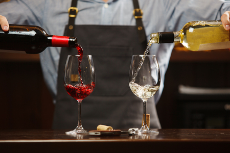 Male sommelier pouring red and white wine into long-stemmed wineglasses. Waiter with two bottles of alcohol beverage. Bartender at bar counter