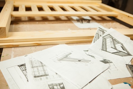 Drafts of wooden bed on pieces of paper at wooden background